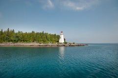 Vit fyr på sjösida för stenig ö Arkivbild