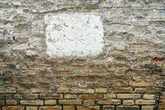Vit fyrkant i mitt av en tegelstenvägg, royaltyfri fotografi