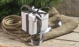 Vit gåvaask med den gråa band, cristmasträdfilialen och repet Royaltyfria Foton