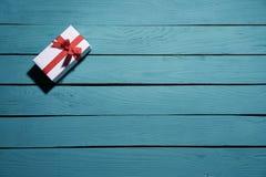 Vit gåvaask med den röda pilbågen på blåa träplankor royaltyfri bild
