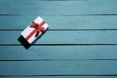 Vit gåvaask med den röda pilbågen på blåa träplankor fotografering för bildbyråer