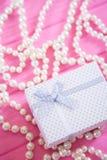 Vit gåvaask som omges av den pärlemorfärg halsbandet på rosa träbakgrund Royaltyfri Bild