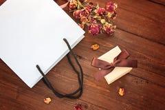 Vit gåvapacke och gåvaask med en pilbåge på en träbackgroun Arkivbild