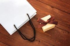 Vit gåvapacke och gåvaask med en pilbåge på en träbackgroun Royaltyfri Foto