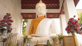 Vit gammal Buddhastaty framme bredvid den gamla Vihara korridoren på Wat Rakhang Khositaram Temple, Thailand Royaltyfria Bilder