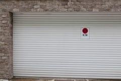 Vit garagedörr med inget parkera tecken royaltyfria foton