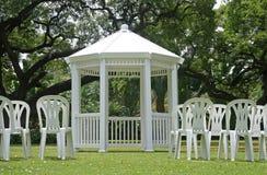 Vit gazebo med stolar utomhus Arkivbild