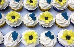 Vit glaserade muffin med solrosor och blåtthjärtor Arkivbild