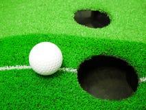 Vit golfboll på torva arkivbild
