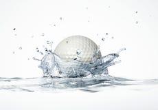 Vit golfboll som plaskar in i vatten som bildar en kronafärgstänk. Arkivbild