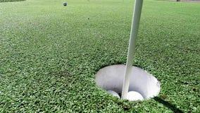 Vit golfboll som slår flaggapinnen och faller in i hålet på sättande gräsplan