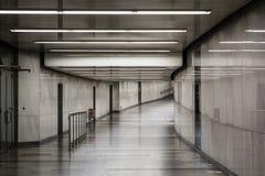 Vit-grå färger rum Belysning i en lång korridor Ljust väggar och golv lyster Bakgrund arkivfoton