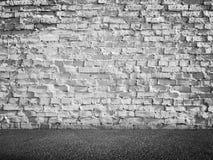 Vit grungy tegelstenvägg och mörkt asfaltgolv Arkivfoto