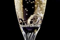 Vit guld- diamantbr?llopcirkel med platina i ett champagneexponeringsglas Br?llop erbjudande som en g?va f?r valentin dag arkivbilder