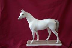 Vit häst för porslinstatyett på en röd bakgrund Arkivbild
