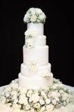 Vit högväxt bröllopstårta med blommor Arkivfoton