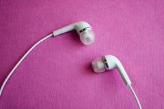 Vit hörlurar för härligt modernt digitalt plast- vakuum med trådar för att lyssna till musik på en purpurfärgad rosa bakgrund kop arkivbild