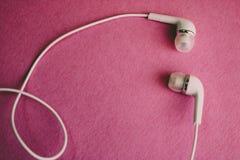 Vit hörlurar för härligt modernt digitalt plast- vakuum med trådar för att lyssna till musik på en purpurfärgad rosa bakgrund kop arkivfoton