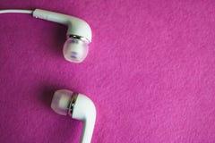 Vit hörlurar för härligt modernt digitalt plast- vakuum med trådar för att lyssna till musik på en purpurfärgad rosa bakgrund kop royaltyfria foton