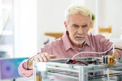 Vit-haired hög man som kontrollerar kapacitet av skrivaren 3D Royaltyfri Foto