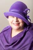 Vit-haired kvinna i purpurfärgad hatt och sjal Royaltyfri Bild