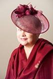 Vit-haired kvinna i röd hatt och halsduk Arkivbild