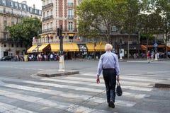 Vit-haired man som korsar gatan på fot- bana för sebra i södra Paris royaltyfri fotografi
