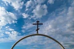 Vit halv-cirkulär båge av järnröret med det mörka ortodoxkorset på det mot den blåa himlen med moln Royaltyfri Foto