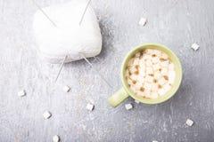 Vit handarbeteboll och kopp kaffe för visare itu med marshmallowen på grå bakgrund Top beskådar kopiera avstånd Handarbetegarn Royaltyfria Foton