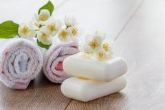 Vit handdukar och tvål för badrumtillvägagångssätt och blommor av jas Royaltyfria Foton