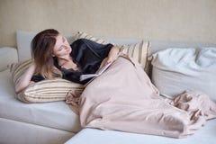 Vit hemtrevlig säng och härlig en flicka som läser en bok, begrepp av hemmet och komfort arkivfoton