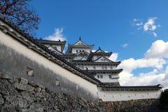 Vit Himeji slott och väggen på bakgrund för blå himmel Himeji slott också som är bekant som den vita hägerslotten arkivfoto