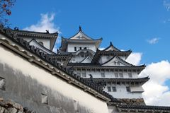 Vit Himeji slott och väggen på bakgrund för blå himmel Himeji slott också som är bekant som den vita hägerslotten arkivbild