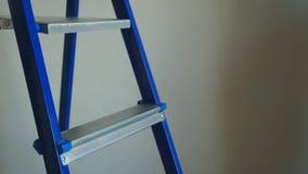 Vit hjälm och blå metallstege i aparmentkonstruktionsplats lager videofilmer