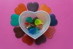 Vit hjärta med hjärtor som omges av hjärtor på rosa färg-malvafärgad backg Royaltyfri Fotografi