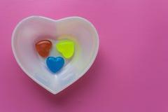 Vit hjärta med tre hjärtor på rosa färg-malvafärgad bakgrund valentin Royaltyfri Fotografi