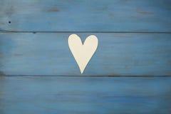 Vit hjärta på en blå bakgrund, trä målade grekblått royaltyfri fotografi