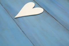 Vit hjärta på en blå bakgrund, trä målade grekblått arkivbild