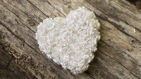 Vit hjärta som göras av små pappers- blommor på trätabellen Arkivfoto