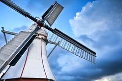 Vit holländsk väderkvarn över blå himmel Arkivbild