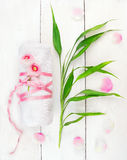 Vit hoprullad handduk med rosa färgblommor och bambuskott Arkivfoto