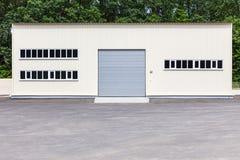 Vit industribyggnadfasad med den gråa rullslutareporten Arkivfoton