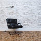 Vit inre för tegelstenvägg med den svarta läderkontorsfåtöljen Arkivfoto
