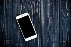 Vit isolerade skärmsmartphonemodellen på den svarta trätabellen Fotografering för Bildbyråer