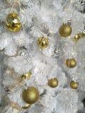 Vit julgrangarnering, variation av guld- hängande bollprydnader med vitt glitter Royaltyfri Foto