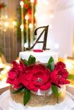 Vit kaka för två våning med blommor, bokstaven A och en guld- list på bakgrunden av blommor och kulor royaltyfri bild