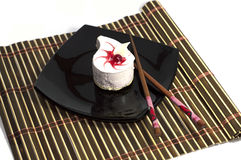 Vit kaka i form av en droppe, på en svart platta Royaltyfria Bilder
