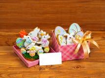 Vit kanin för påskkakor och kulöra ägg i askar för en gåva Arkivbild
