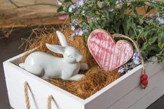 Vit kanin och hjärta i en blomma boxas Arkivbilder