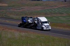 Vit Kenworth Halv-lastbil som drar andra nya Halv-lastbilar Arkivfoton